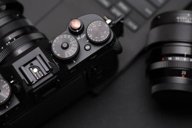 spiegellose digitalkamera, objektiv und laptop am schreibtisch. konzept der fotograf arbeitsraum - kreativer speicher stock-fotos und bilder