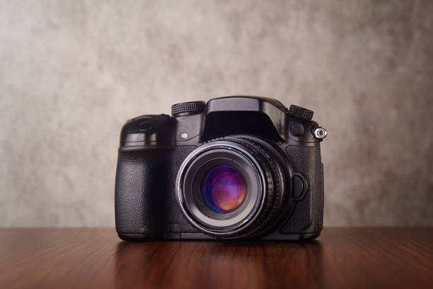 Digital mirrorless professional camera on wooden table with concrete wall as a background stock photo