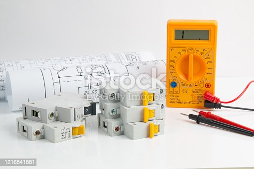 Digital multimeter and circuit breaker with paper drawings on white table
