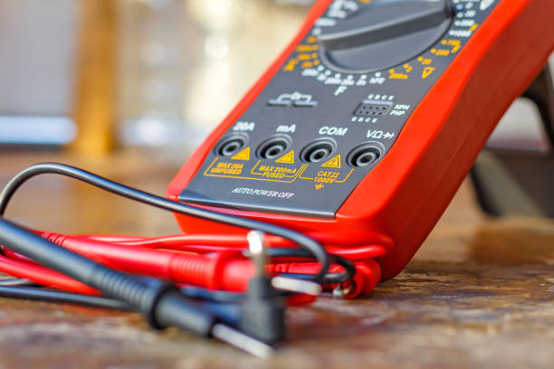 Digital multimeter with probes on a wooden table in the workshop stock photo