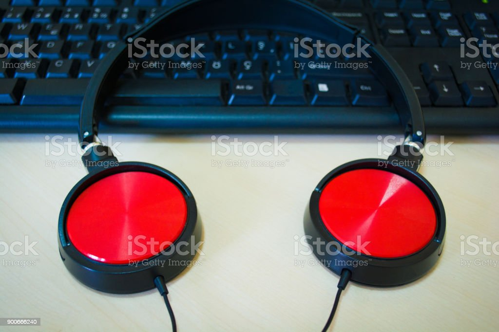 digital music creation theme with professional red headphones on the computer keyboard stock photo