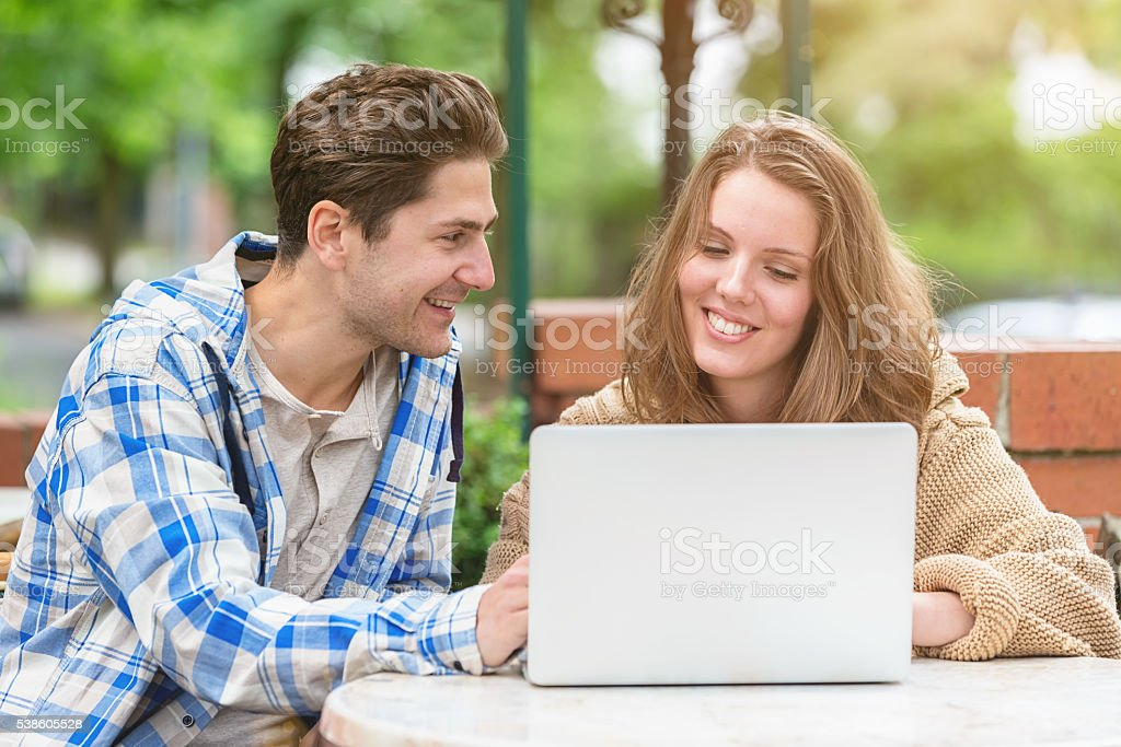 Digital Natives Couple Blogging Together in Outdoor Street Cafe stock photo