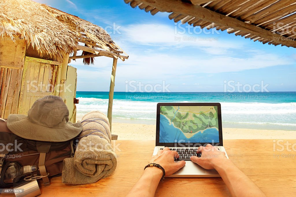 Digital nomad working at computer from a tropical beach stock photo