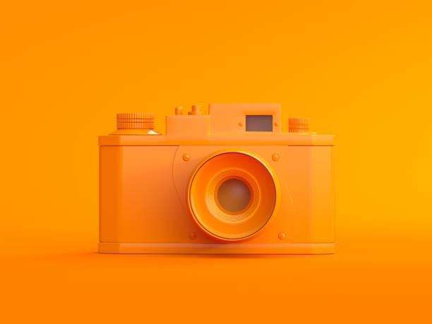 3d digital orange fotokamera auf orangefarbenem hintergrund - farblinsen stock-fotos und bilder
