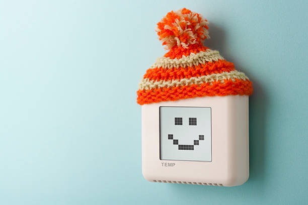 digital room temperature thermostat with smiley face and wooly hat - warm house stock photos and pictures
