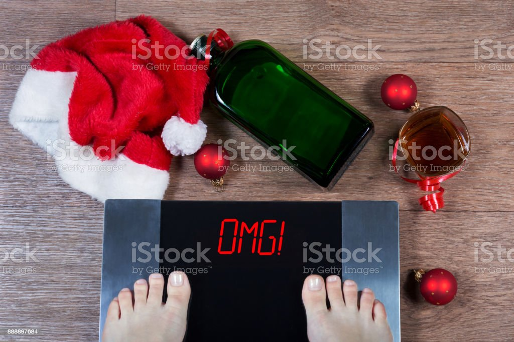 Digital scales with female feet on them and sign 'omg!' surrounded by Christmas decorations, bottle and glass of alcohol. Concept of consequences of unhealthy lifestyle stock photo