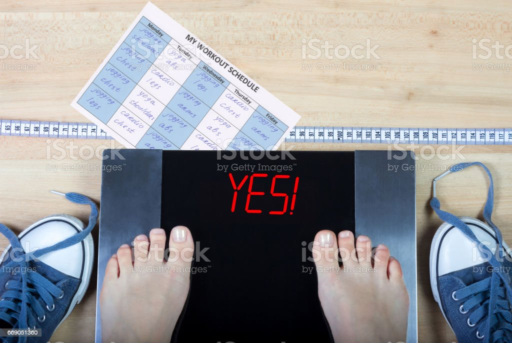 Digital scales with female feet on them and sign'yes!' surrounded by gymshoes, workout schedule and measuring tape. stock photo