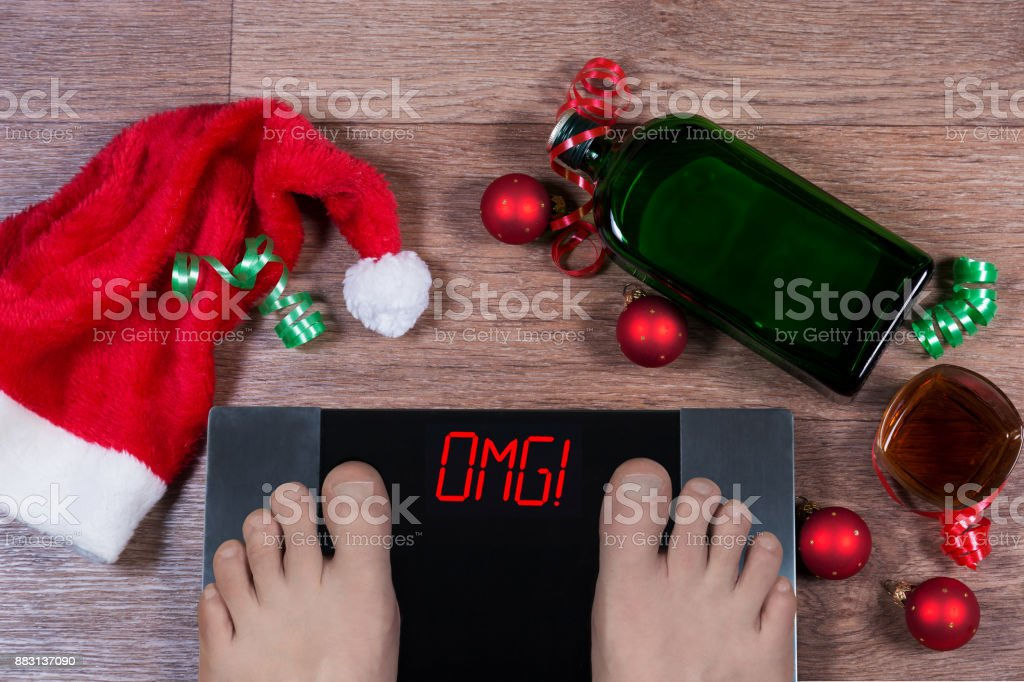 Digital scales with male feet on them and sign 'omg!' surrounded by Christmas decorations, bottle and glass of alcohol. Shows how unhealthy lifestile during holidays effects our body. stock photo
