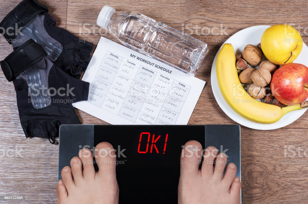 Digital scales with male feet on them and sign'ok' surrounded by bottle of water, plate with healthy food, workout schedule paper and  weightlifting gloves. Concept of healthy lifestyle. stock photo