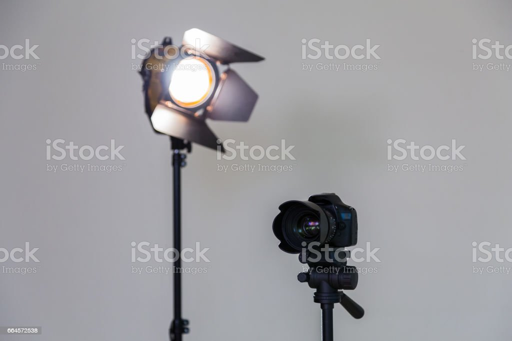 Digital SLR camera and a spotlight with a Fresnel lens on a gray background. Shooting in the interior. Equipment for the production of films stock photo