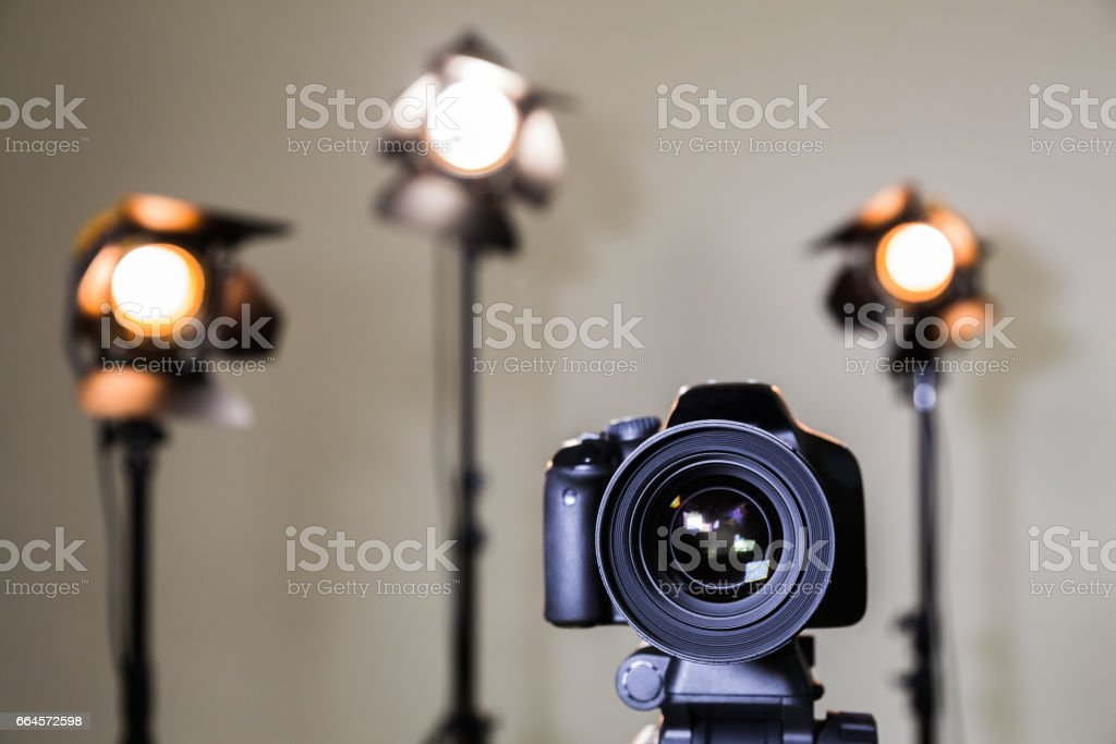 Digital SLR camera and three spotlights with Fresnel lenses. Manual interchangeable lens for filming. Shooting in the interior with artificial light. Equipment for movies stock photo