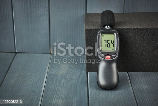 Digital sound level meter with display and control buttons on acoustic foam