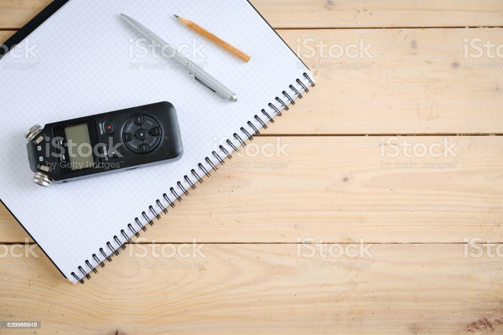Digital sound recorder and other accessories on the wooden table, stock photo