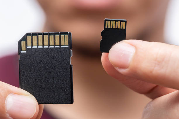 digital storage memory size matter concept,sd card and micro sd card compare on handle - memory card stock photos and pictures