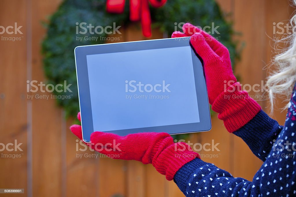 Digital tablet against christmas ornaments Close up of digital tablet held by female hands wearing red gloves against christmas ornaments. Adult Stock Photo