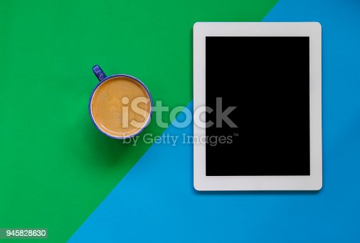 Digital Tablet and coffee on color block background