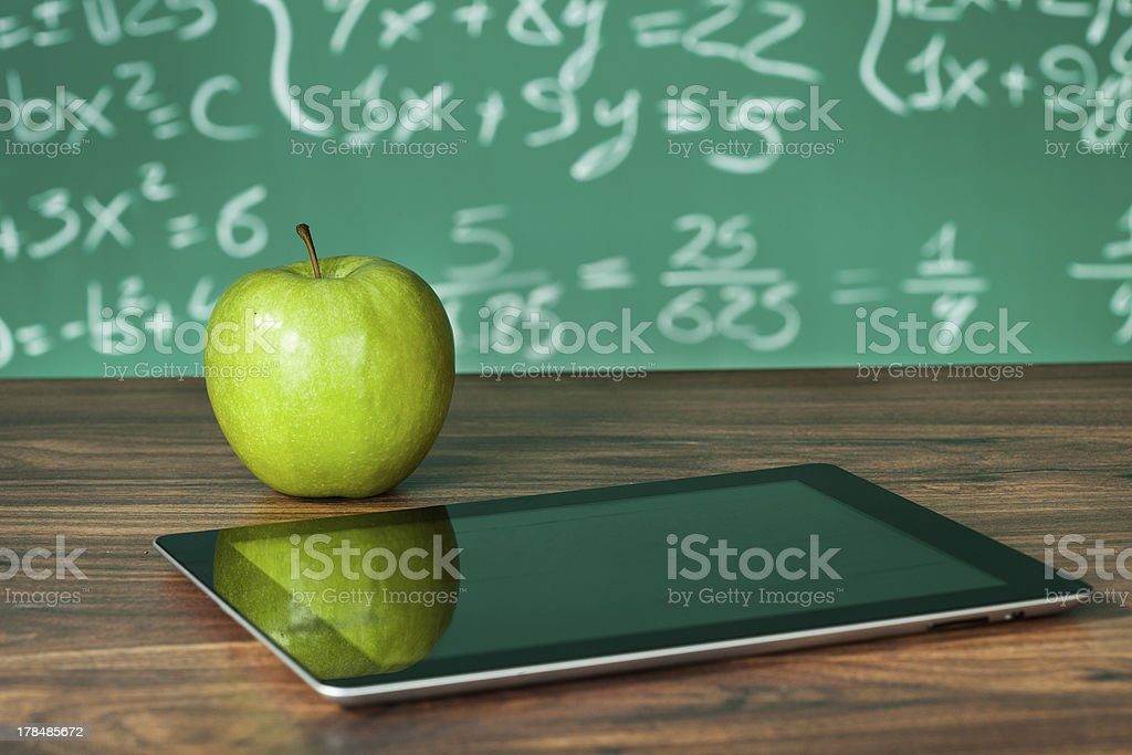 Digital tablet and a green apple on a desk by a blackboard stock photo