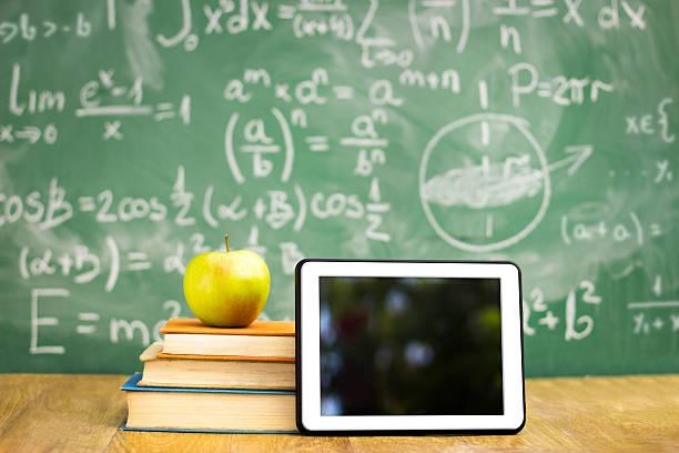 digitale tablet und apple auf stapel bücher - kreide farbe schreibtisch stock-fotos und bilder