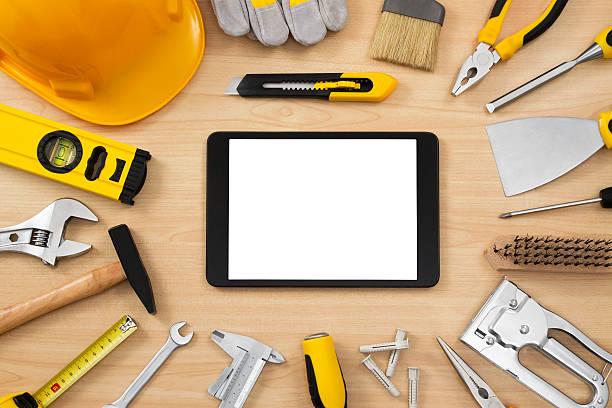 digital tablet and assortment of carpentry tools on table - skulpturprojekte stock-fotos und bilder