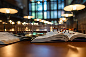 istock Digital Tablet and Eyeglasses On Books in Public Library 1135144614