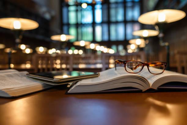 tableta digital y anteojos en libros en la biblioteca pública - biblioteca fotografías e imágenes de stock