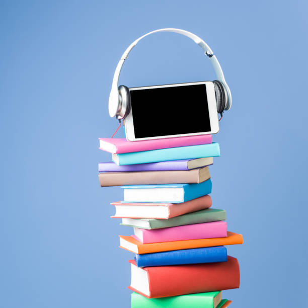 Digital Tablet And Headphone On Stack Of Multicolored Books stock photo