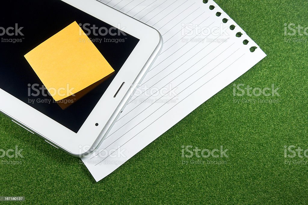 Digital tablet and note paper on green grass royalty-free stock photo