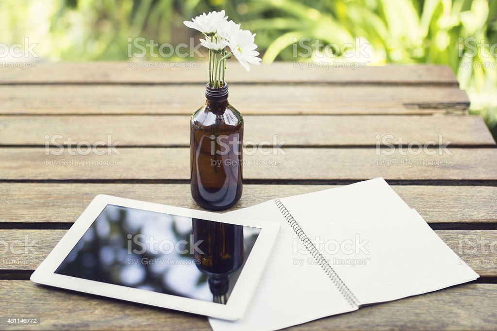 Digital tablet and notebook on a wooden table outdoors stock photo