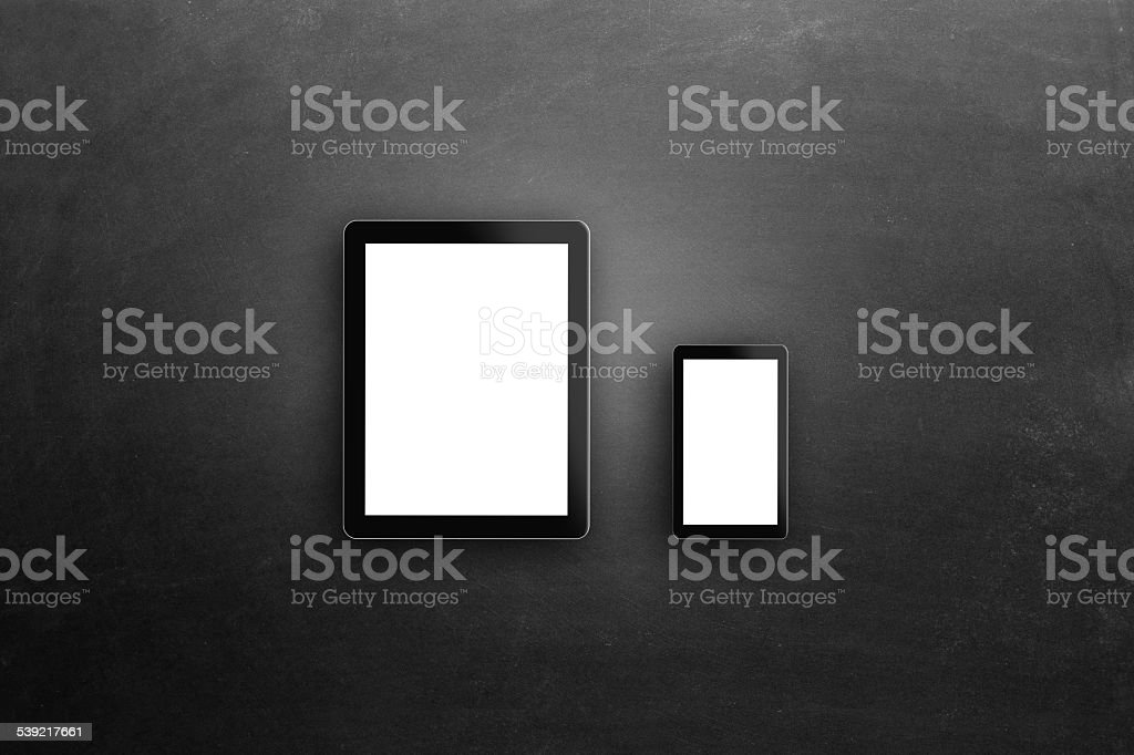 Digital tablet and smart phone on blackboard stock photo