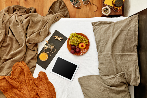 Digital tablet and some snacks with fruit plate on empty and messy bed - Cut out screen