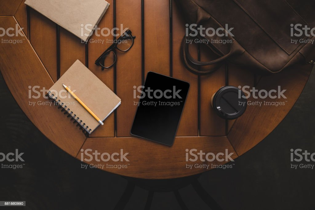 digital tablet and supplies on wooden table stock photo