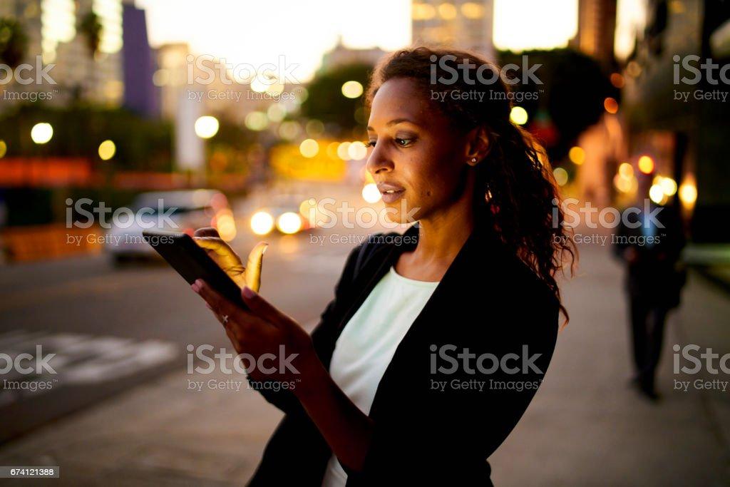 數位平板電腦在晚上在城市。 免版稅 stock photo