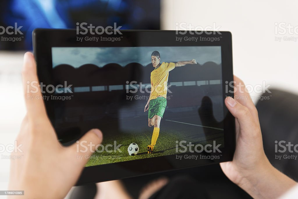 Digital tablet being used to watch a football match royalty-free stock photo