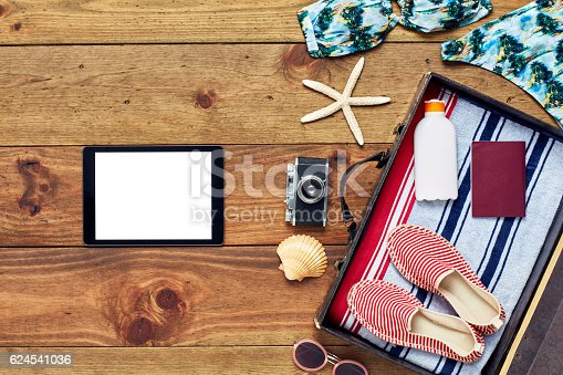 941183588 istock photo Digital tablet by open suitcase with summer vacation accessories 624541036