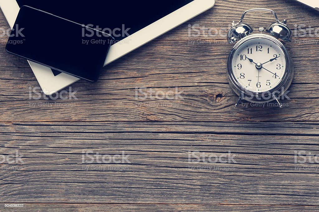 Digital tablet, clock and smart phone on a wooden table. stock photo