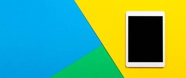 Digitaler Tablet-Computer auf hellblauem, grünem und gelbem Hintergrund. Ansicht von oben – Foto