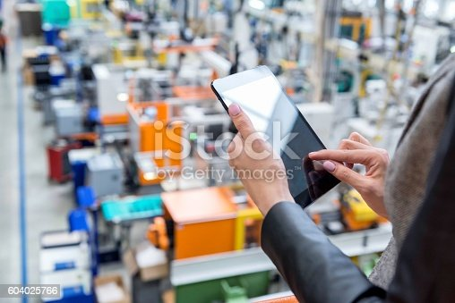 istock Digital tablet & Futuristic factory 604025766