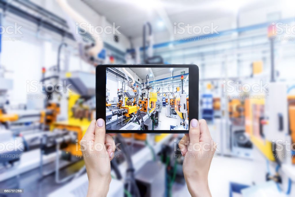 Digital tablet & futuristic industrial machinery stock photo