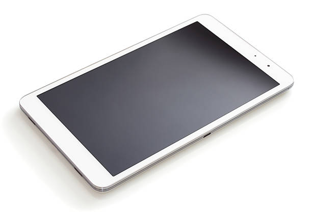 digital tablet lying on a white table - diminishing perspective stock photos and pictures