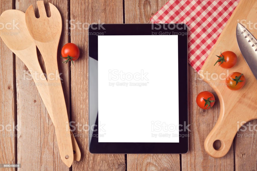Digital tablet mock up template with cooking utensils and tomatoes. View from above stock photo