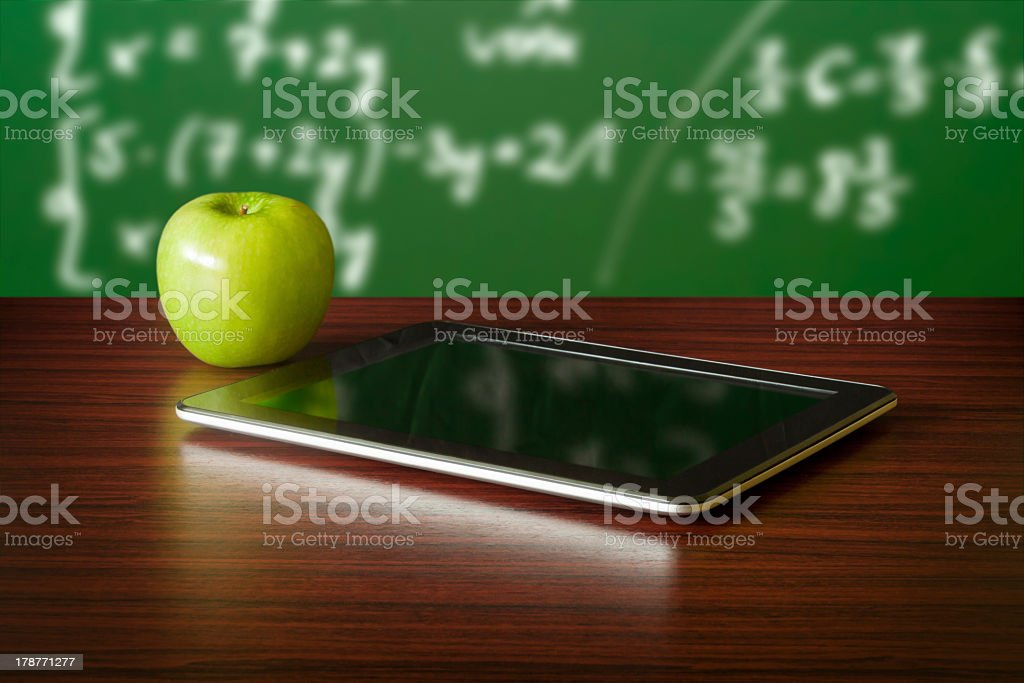 Digital tablet on a table next to a green apple stock photo
