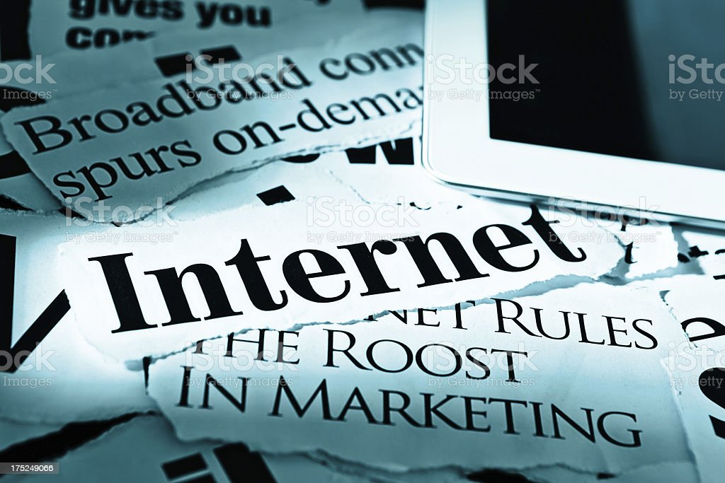 Digital tablet on headlines about internet, marketing, and broadband connectivity stock photo