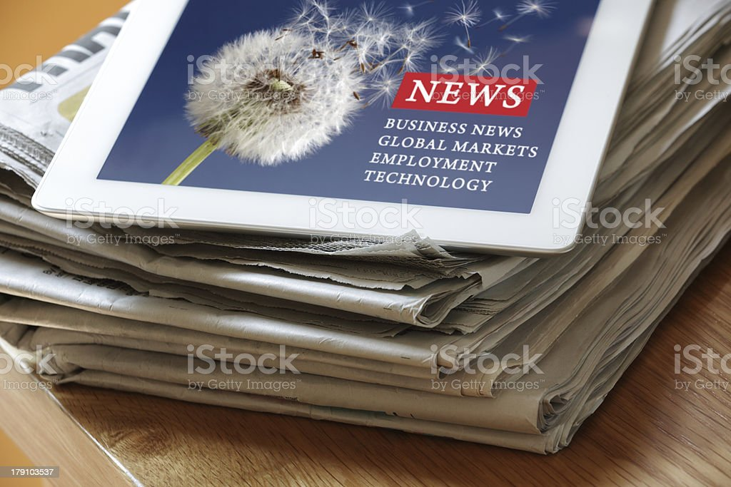 Digital tablet on newspaper royalty-free stock photo