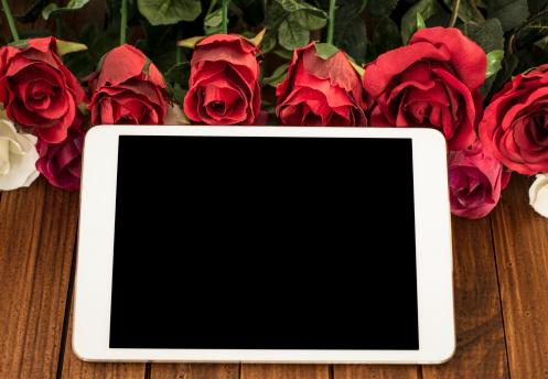 Digital tablet on St. Valentine decoration background