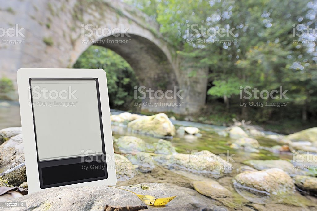 Digital tablet outdoors by river stock photo