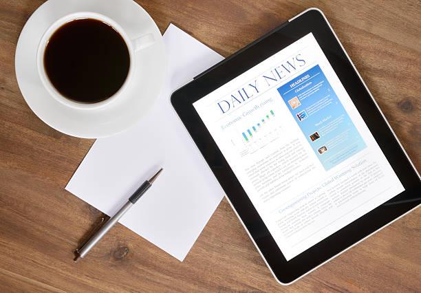 digitale tablet-pc mit nachrichten auf schreibtisch (xxxl) - www kaffee oder tee stock-fotos und bilder