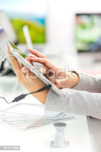 Unrecognizable woman shopping for digital tablet in electronics store, copy space