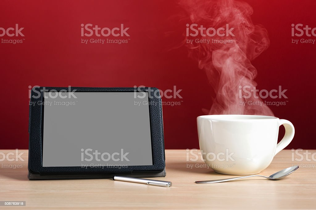 Digital Tablet with a large steamy cup of coffee stock photo