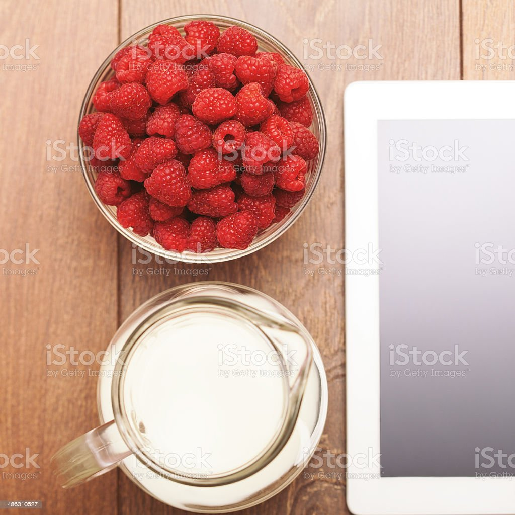 Digital tablet with milk and raspberry royalty-free stock photo