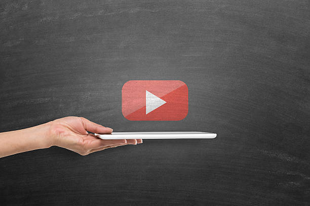 Digital tablet with you tube play icon on blackboard stock photo